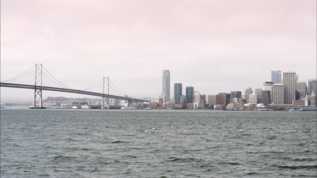 static shot of the oakland bay bridge and san francisco. - san francisco oakland bay bridge stock videos and b-roll footage