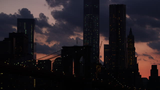 Static shot of the One World Trade Center, Brooklyn Bridge and silhouettes of Manhattan, whilst a helicopter passes by against the dusk sky.