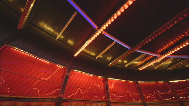 static shot of the red bulbs of a fairground waltzer ride flashing on and off, creating abstract patterns on the plastic windows behind, uk. - fairground ride stock videos & royalty-free footage