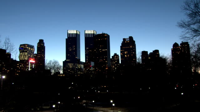 static shot of the time warner center surrounded by high rise apartments along central park west as seen from central park at dusk - time warner center stock videos & royalty-free footage