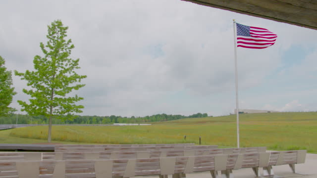 static shot of the visitor center with a waving american flag at the flight 93 memorial site - pennsylvania stock-videos und b-roll-filmmaterial