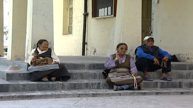 static shot of tibetans holding prayer beads and a prayer wheel sitting on the steps of the library of tibetan works which holds over 80000 buddhist... - traditionally tibetan stock videos & royalty-free footage