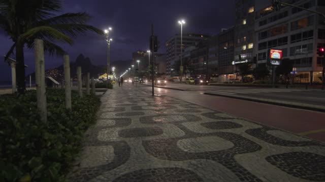 static shot of traffic and sidewalk pattern in copacabana. - copacabana stock videos & royalty-free footage