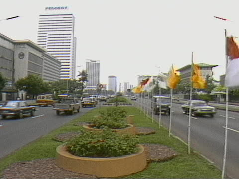 static shot of traffic passing either side of median with flags and landscaping in jakarta - median nerve stock videos & royalty-free footage