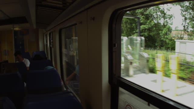 Static shot of train interior as it comes to a stop at a depot