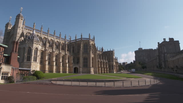 vídeos de stock e filmes b-roll de static shot of two white vans driving between st george's chapel where prince harry and meghan markle have announced they will be married and windsor... - berkshire inglaterra