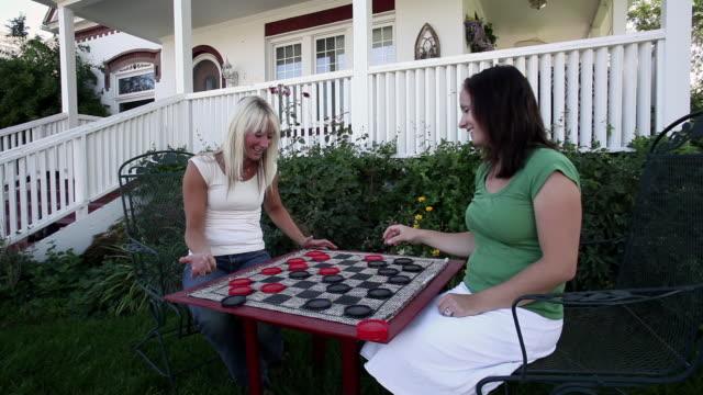vídeos y material grabado en eventos de stock de static shot of two women playing checkers. - falda