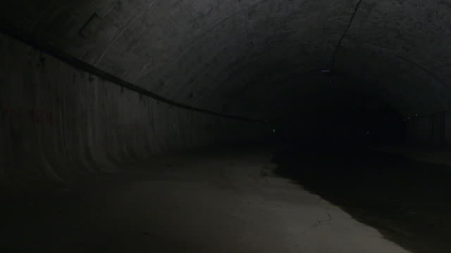 static shot of water lapping the edges of a tunnel in a sewer in austria. - sewage stock videos and b-roll footage