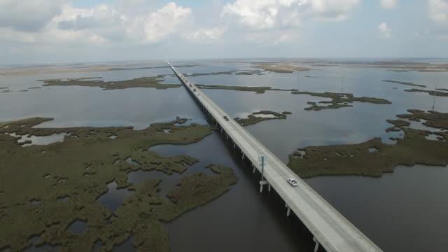 static shot over causeway - Drone Aerial 4K Lake Pontchartrain CausewayGrand Isle Louisiana coast Mississippi river bridge and barge everglades, gulf delta, with wildlife 4K Transportation