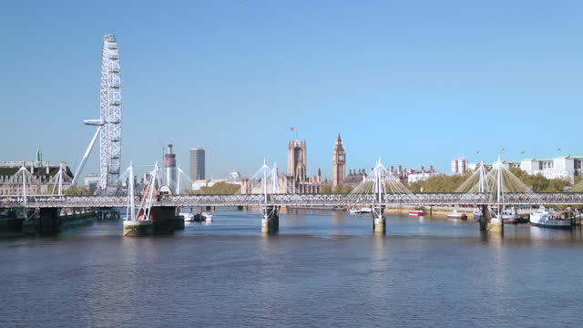 static shot over the thames facing hungerford and golden jubilee bridges, the london eye, and the palace of westminster on blue sky day. - hungerford bridge stock videos & royalty-free footage