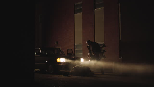 vidéos et rushes de static shot reenactment of a man pulling out another one from the car then grappling with each other during the 1980s - crime