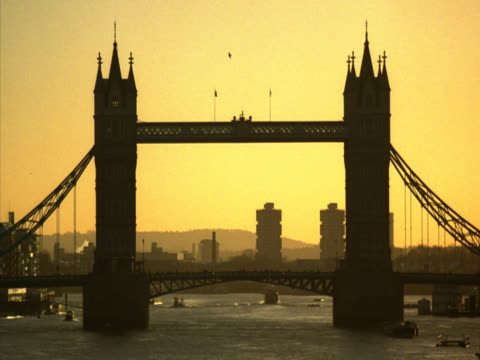 static shot showing tower bridge at sunset. in the foreground, in close-up, the shot is momentarily obscured by passing pedestrians. london, uk - unknown gender stock videos & royalty-free footage