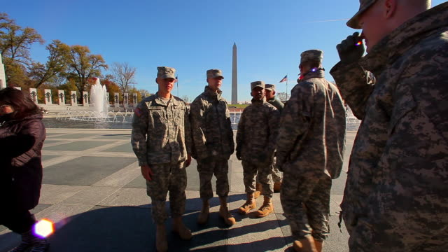 A static shot with a lens flare of soliders posing for a photo by the WWII Memorial.