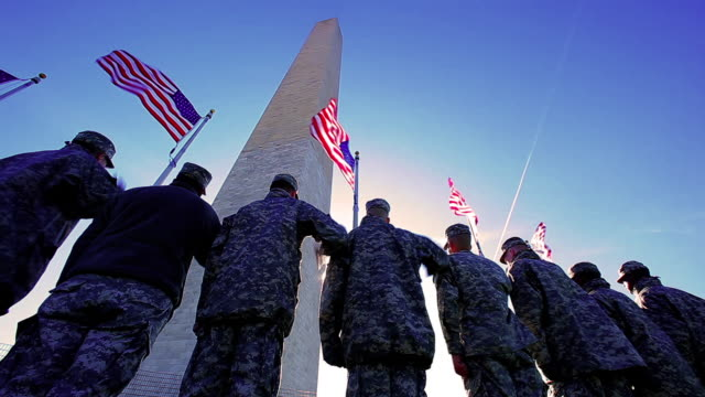 A static shot with a lens flare of the back of a group of soldiers at the Washington monument.