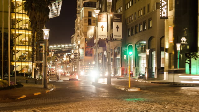 static timelapse at night at a busy intersection of the nightlife and people buzzing in johannesburg, south africa at the sandton convention centre - ヨハネスブルグ点の映像素材/bロール
