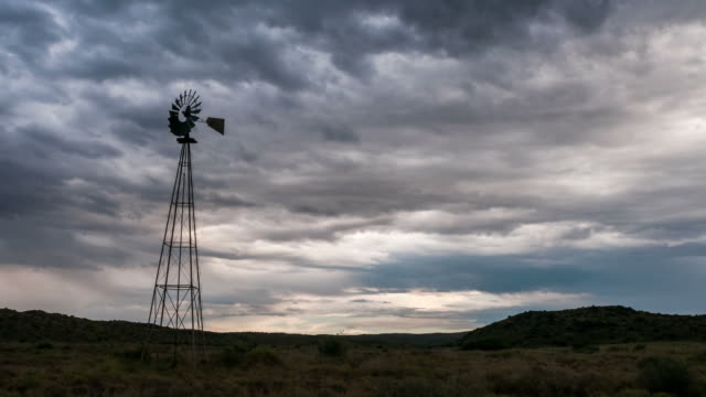 vidéos et rushes de static timelapse of a frantically blowing windmill silhouetted against a dramatic and stormy sky with thunder and lightning in a typical karoo landscape - karoo