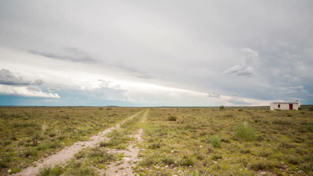 vidéos et rushes de static timelapse of a typical karoo farm landscape with a small house next to a fence post, scattered clouds in a vast open scene - karoo