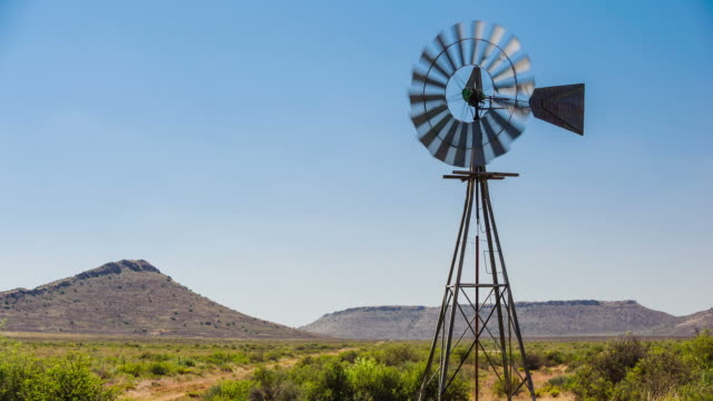 vidéos et rushes de a static timelapse of a typical karoo landscape scene filled with shrubs and grass, a windmill blowing frantically in the wind against a bright blue sky and hills in the background - karoo