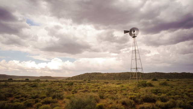 vidéos et rushes de static timelapse of a windmill with cumulus clouds and formations blowing frantically in the wind against a dark and stormy sky in a typical karoo landscape - karoo