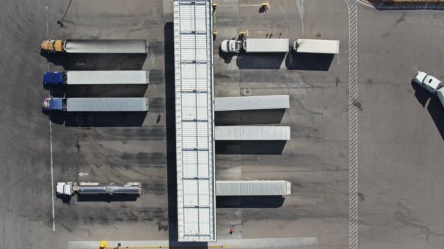 static top down drone shot of trucks pulling up to fuel pumps at truck stop truck stop - trasporto merci via terra video stock e b–roll