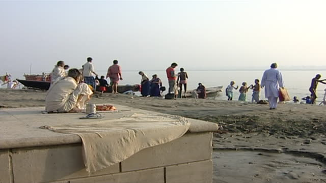 static view of the indians performing morning prayers and ritual ablutions by the riverbank in varanasi - barefoot stock videos & royalty-free footage