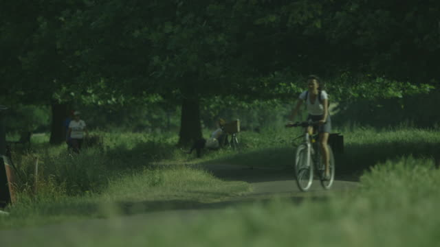 Static wide shot of a woman cycling along a footpath bordering the River Cam on Stourbridge Common in Cambridge, UK.