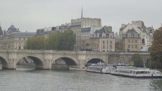 Static wide shot of tourboats stationed next to the Pont Neuf, Paris, France.