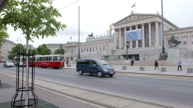 static wide shot of trams and cars passing the austrian parliament, vienna. - austria flag stock-videos und b-roll-filmmaterial