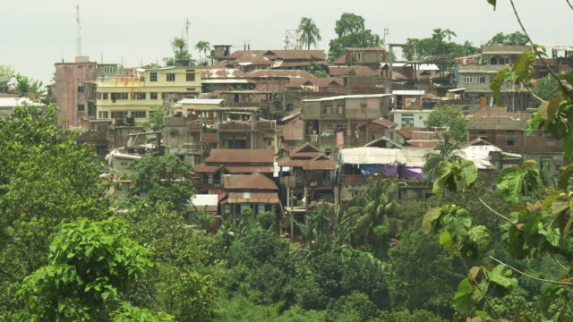 Static wide shot showing houses on a hillside in Guwahati in Assam, India.