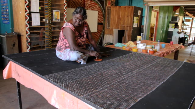 ms static woman sitting on large canvas creating abstract tiwi art / northern territory, australia - tiwi people stock videos & royalty-free footage