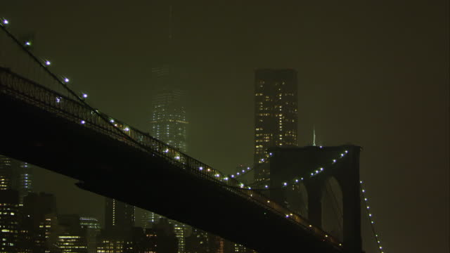 static zoomed view at night overlooking the east river and the brooklyn bridge. - brooklyn bridge stock videos & royalty-free footage