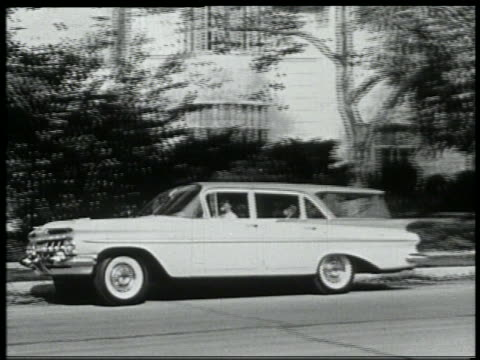 b/w 1959 pan station wagon pulling away from curb + driving down suburban street - 1959 stock videos & royalty-free footage