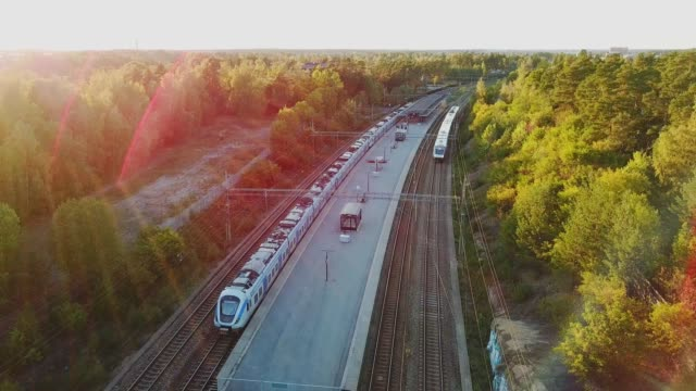 stationary and passing train at trainstation helenelund, sollentuna, stockholm - commuter train stock videos & royalty-free footage