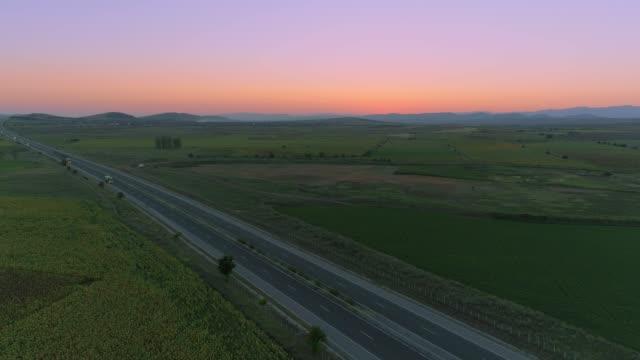 stationära drone sköt över motorvägen trafik efter solnedgången - landsväg bildbanksvideor och videomaterial från bakom kulisserna