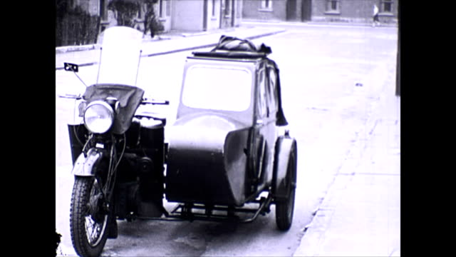 stationary royal enfield motorbike with attached sidecar is parked by the kerb. two children approach and get into the sidecar guided by an adult. - sidecar stock videos & royalty-free footage