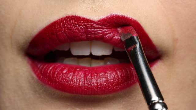 vidéos et rushes de stationary shot of the model applying lipstick.  - red