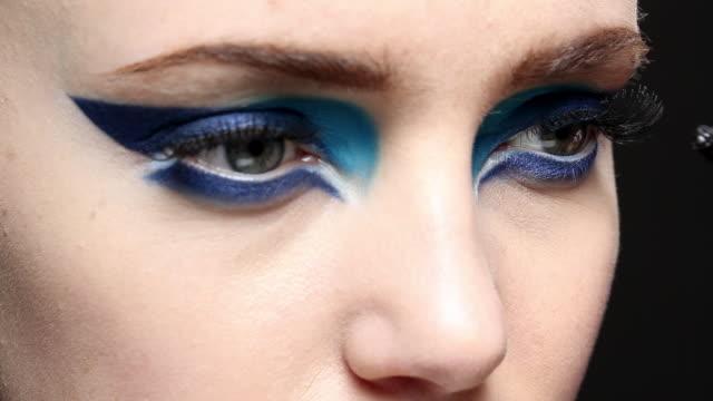 Stationary side shot of the model applying mascara.