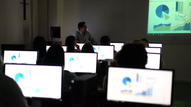 statistics teacher at the computer room teaching his students - aula video stock e b–roll