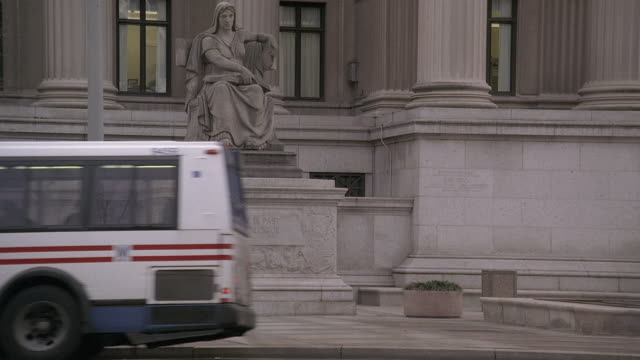 stockvideo's en b-roll-footage met ws statue at the national archives with brick pillars and passing traffic / washington, d.c., united states - national archives washington dc