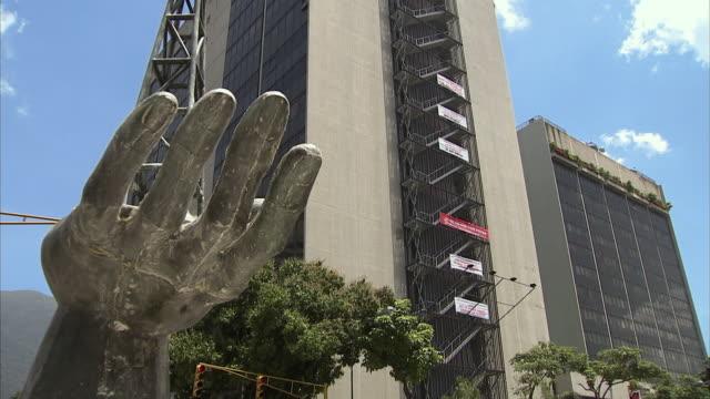 vídeos y material grabado en eventos de stock de ws la tu statue depicting hand holding oil drilling rig in front of pdvsa, state-owned oil company, in caracas / metropolitan district of caracas, miranda, venezuela - venezuela