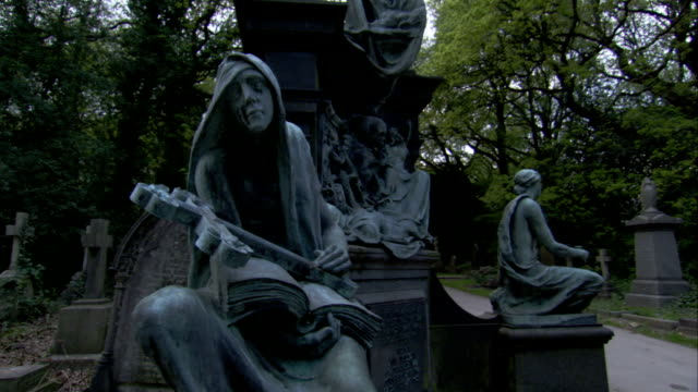 a statue depicts a figure holding a book with a cross laid on top of it in lawnswood cemetery. available in hd. - leeds stock videos and b-roll footage