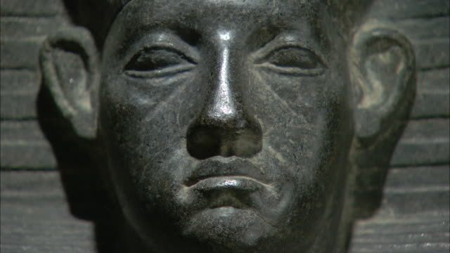 A statue depicts a frowning face with large ears in Luxor, Egypt.