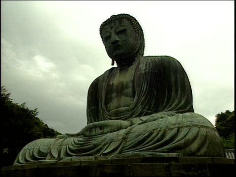 a statue depicts a meditating buddha. - televisione a ultra alta definizione video stock e b–roll