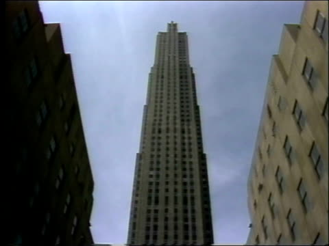 vidéos et rushes de statue flowers people outside rockefeller center / tilt up and down rockefeller center building / pedestrians walk past flags on rockefeller center... - 1982