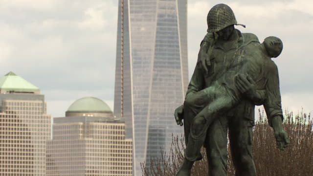 statue in liberty state park depicting solders rescuing holocaust victims from germany in world war two.  the skyscrapers of lower manhattan are behind out of focus. - figura maschile video stock e b–roll