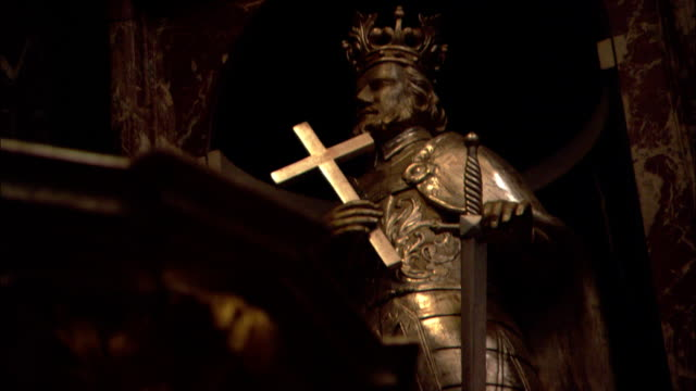 a statue in the cathedral of vilnius holds a cross and a sword. - heiliger stock-videos und b-roll-filmmaterial