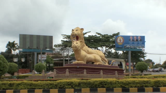 ws zo statue of 2 gold plaster lions in center of roundabout, sihanouksville, cambodia - cambodia stock videos & royalty-free footage