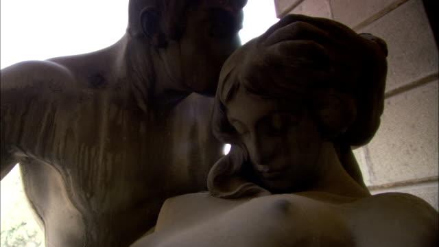 a statue of a man kissing a woman. available in hd. - artigianato video stock e b–roll
