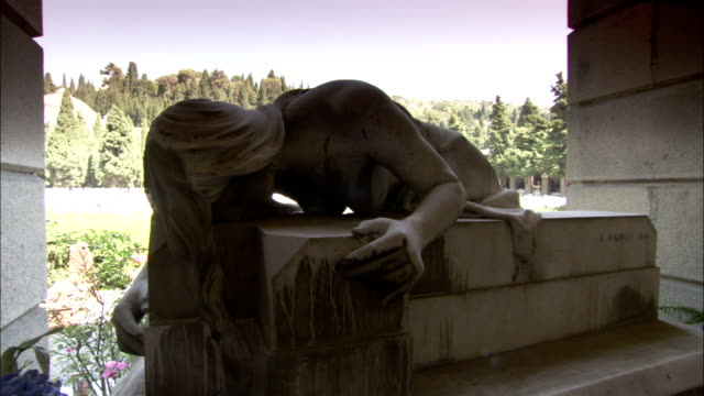 a statue of a naked woman kneels at the cimitero monumentale di staglieno. available in hd. - kneeling stock videos and b-roll footage