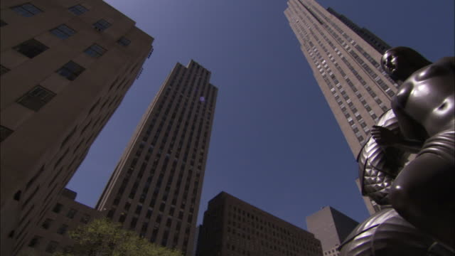 a statue of a naked woman stands in front of the ge building at the rockefeller center. available in hd - ロックフェラーセンター点の映像素材/bロール